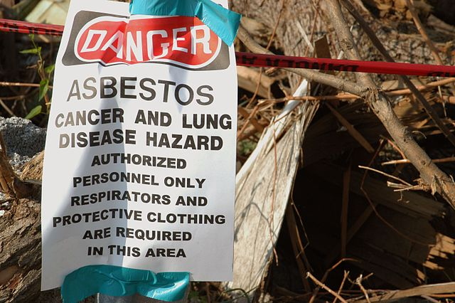 Asbestos caution sign next to pile of debris