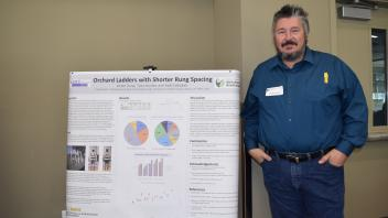 Man stands with hands in his pockets next to his research poster