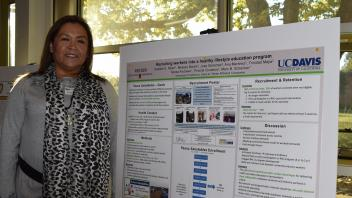 smiling woman with leopard print scarf stands next to her research poster