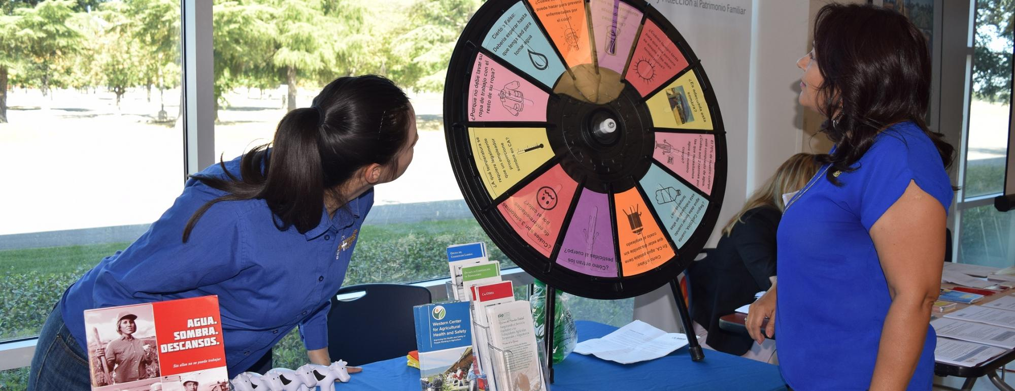 WCAHS Outreach worker play the spin the wheel game with a member of the public visiting the outreach table at an event