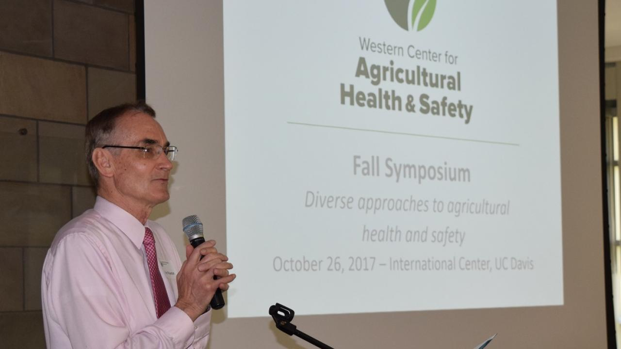 Dr Kent Pinkerton stands at podium with microphone screen in background shows slide with WCAHS logo