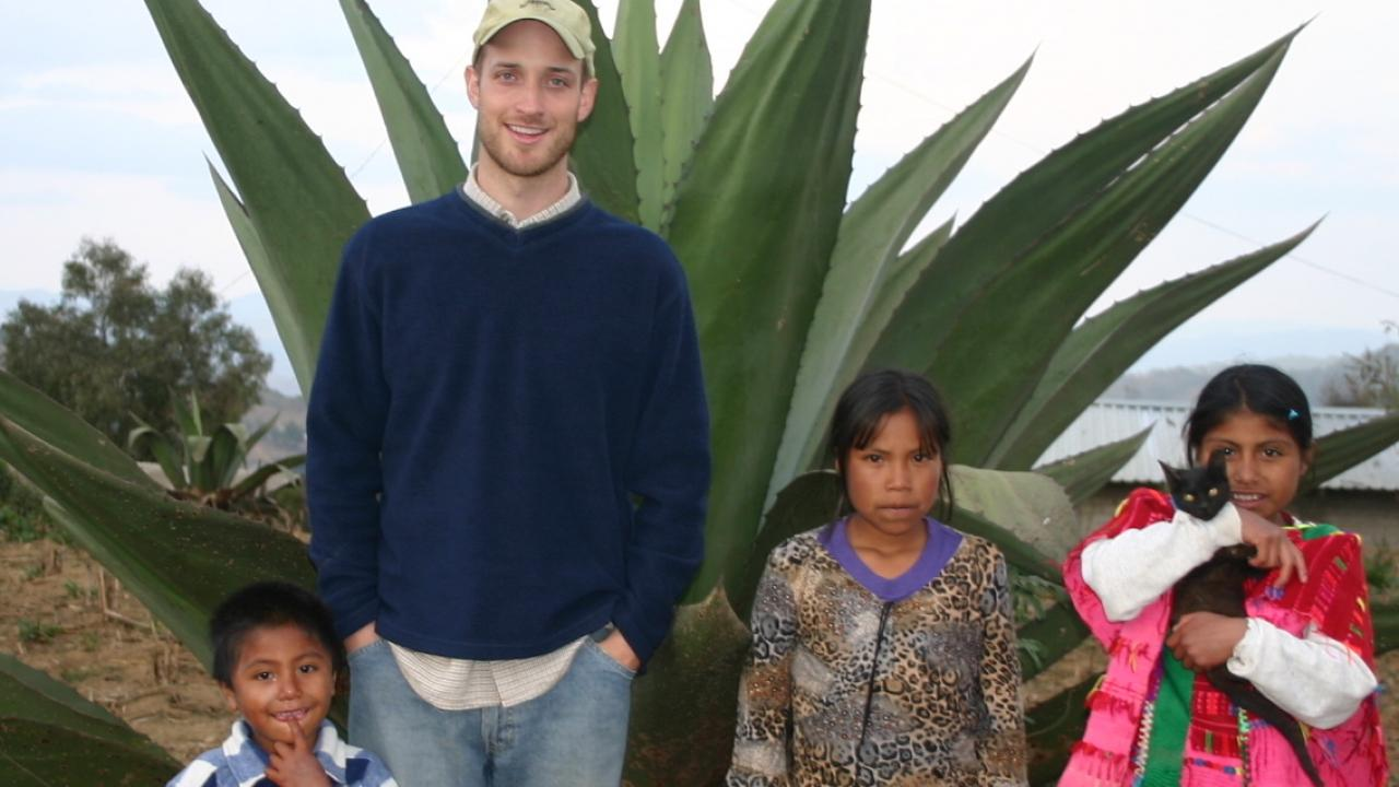 Doctor Holmes standing in front of a large maguey with three Mexican children at his side, smiling at the camera