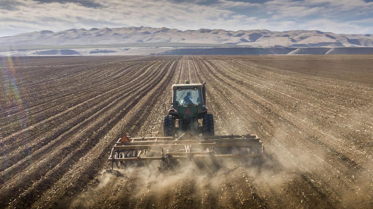 Tractor tills the soil and kicks up dust