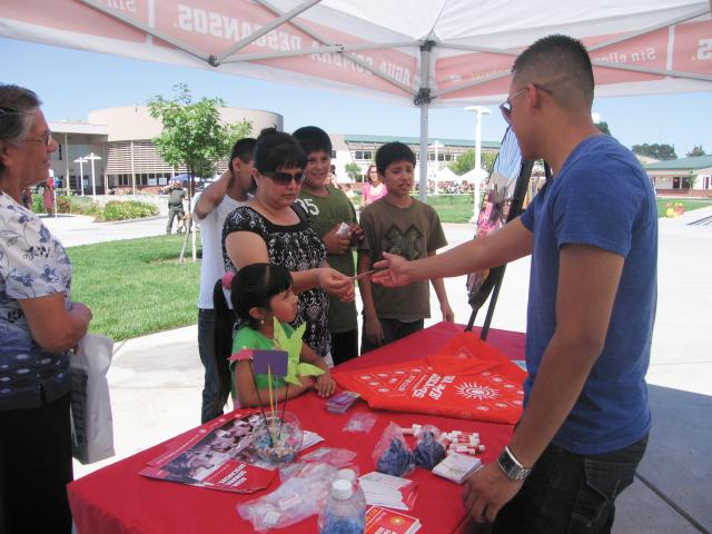 Farm family receives information about preventing heat illness at a WCAHS booth at a community health fair
