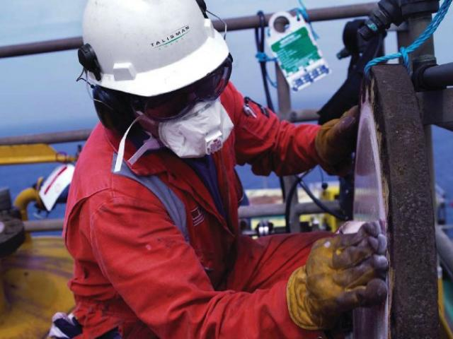 Oil rig worker checks valves wearing eye protection and respirator