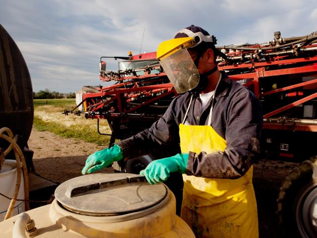 Worker wears PPE to close a barrel of chemicals