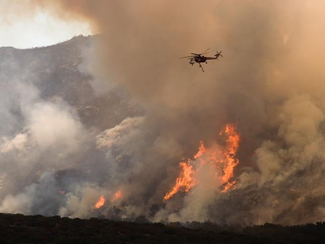 A helicopter drops water on the wildfire in California