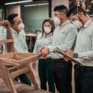 Man in denim shirt wearing a safety mask discusses work issues with associates