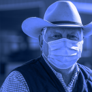 Man wearing a cowboy hat and a face mask