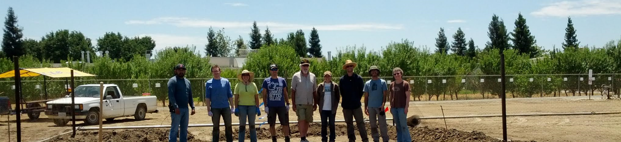 Researchers from biosolarization team posing in front of a bio-solarized plot of land