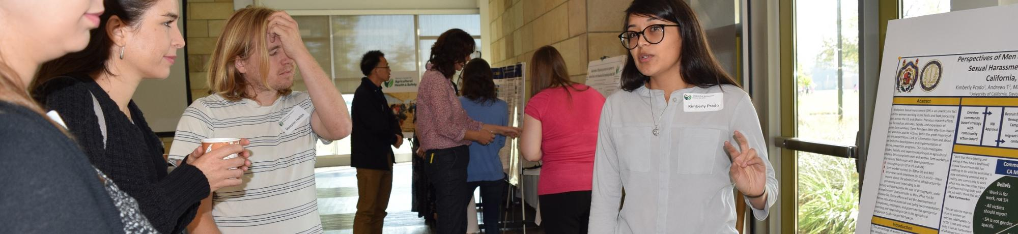 WCAHS Graduate Student Kimberly Prado on right side explains research poster to three women on left side