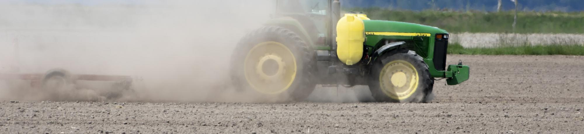 Tractor creating dust in dry field